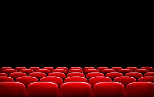 Filas de asientos rojos de cine o teatro frente a una pantalla negra con espacio de texto de muestra.