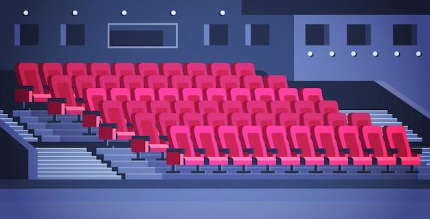 Las filas de los asientos rojos del teatro o del cine están vacíos.