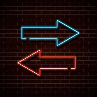 Flechas rojas y azules de neón en una pared de ladrillo.