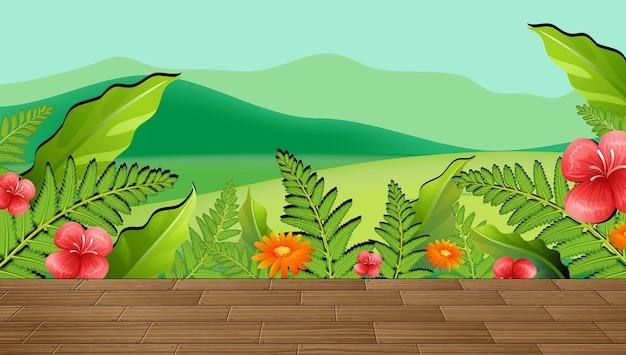 Flor de hibisco y hojas con fondo de montaña.