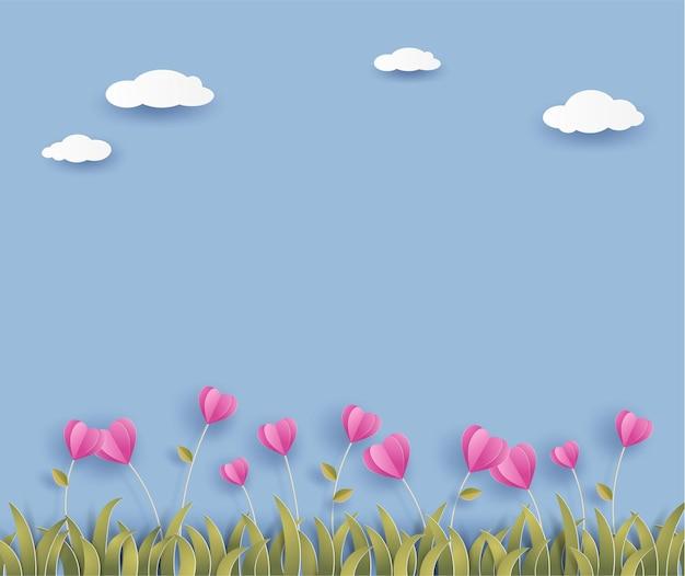 Flor de origami rosa en forma de corazón y hierba sobre fondo azul con nubes.