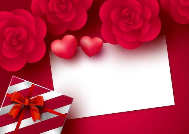 Flores de rosas y tarjeta de papel blanco en blanco con corazón sobre fondo rojo para el día de san valentín