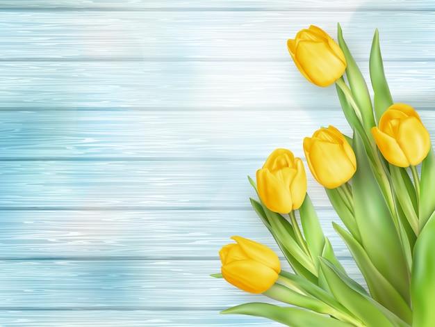 Flores de tulipanes amarillos en tablones de madera.