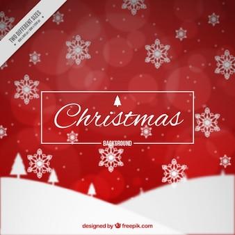 Fondo bokeh rojo de navidad con copos de nieve
