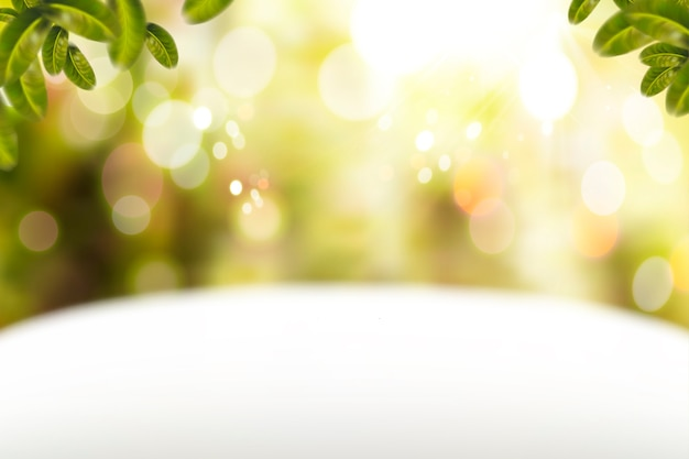 Fondo de brillo con mesa blanca y elementos de hojas verdes
