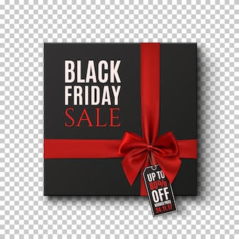 Fondo conceptual de venta de viernes negro. caja de regalo negra con cinta roja y etiqueta de precio sobre fondo transparente.