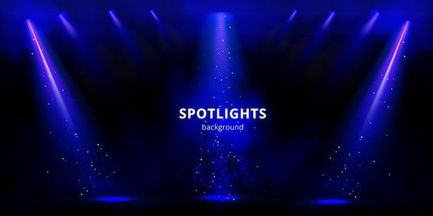 Fondo de focos, rayos de luz de escenario azul con humo y destellos sobre fondo negro.