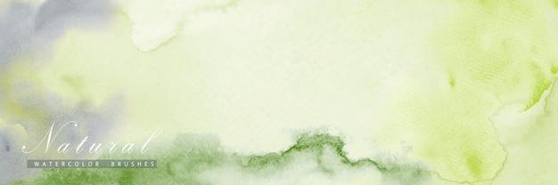 Fondo horizontal abstracto diseñado con manchas de acuarela de color verde.