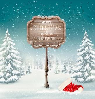 Fondo de invierno hermoso con bosque nevado y un cartel de madera feliz navidad.