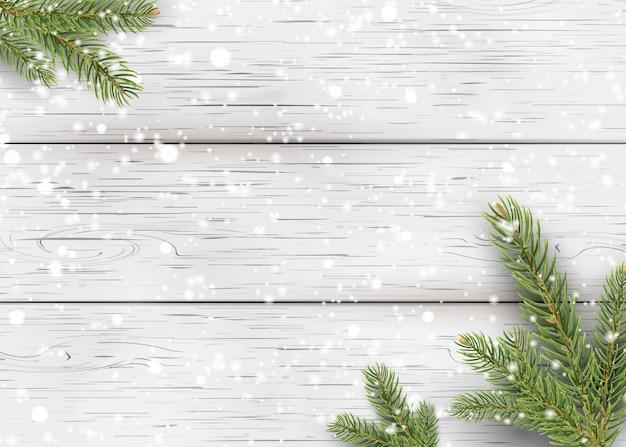 Fondo de madera blanca de navidad con ramas de abeto de vacaciones, cono de pino y nieve brillante que cae. endecha plana, vista superior con espacio para copiar el texto.