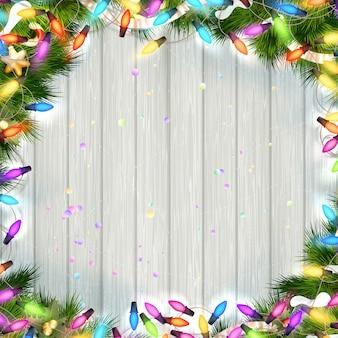 Fondo de madera de navidad con ramas y una guirnalda.