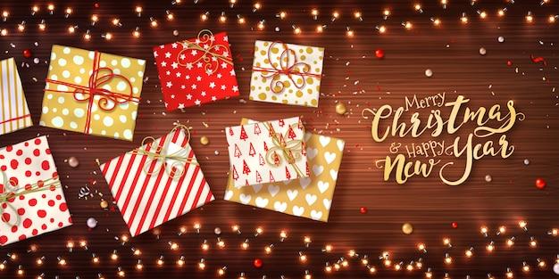Fondo de navidad y año nuevo con cajas de regalo, guirnaldas de luces de navidad, adornos y confeti de brillo en textura de madera.