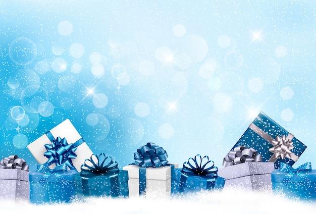 Fondo de navidad azul con cajas de regalo y copos de nieve