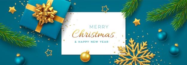 Fondo de navidad con banner de papel cuadrado, caja de regalo azul realista con lazo dorado, ramas de pino, estrellas doradas y copo de nieve, adorno de bolas.