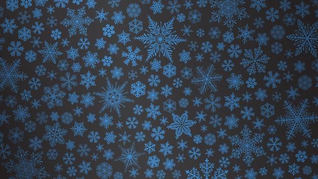 Fondo de navidad de copos de nieve grandes y pequeños en colores azul oscuro