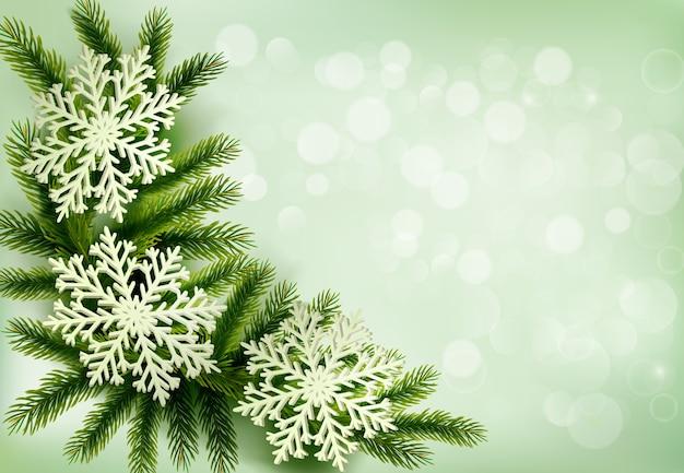 Fondo de navidad verde con ramas de árboles de navidad y copos de nieve.