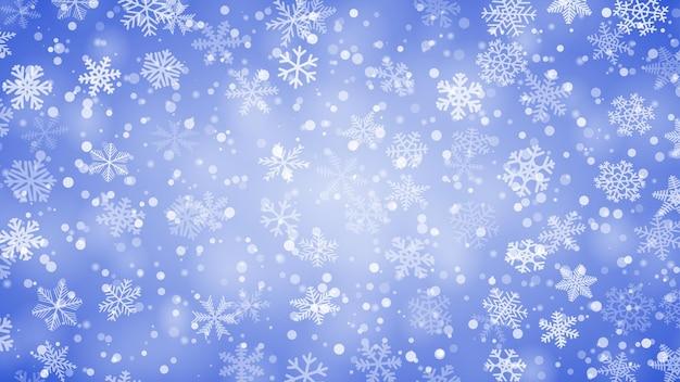 Fondo navideño de copos de nieve de diferentes formas, tamaños y transparencia en colores azules