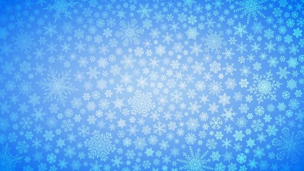 Fondo navideño de copos de nieve grandes y pequeños en colores azul claro