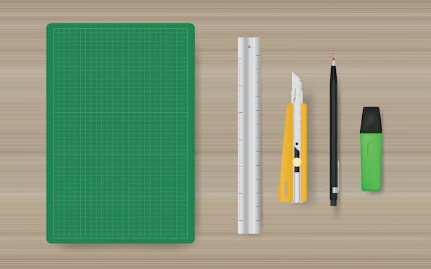 Fondo de objeto de oficina de estera de corte verde con regla, cutter, lápiz y marcador