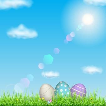 Fondo de pascua con cielo, sol, hierba, huevos de pascua y flores.