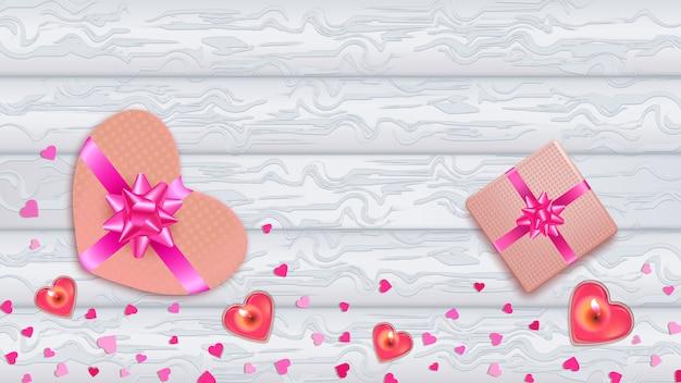 Fondo plano de madera blanca con corazones de color rosa, cajas de regalos y velas.