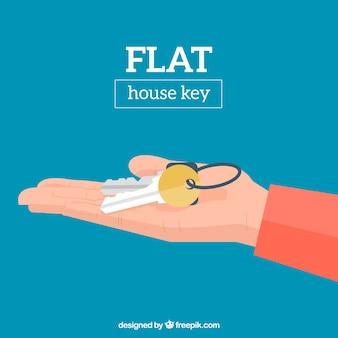 Fondo plano de mano sosteniendo llave de casa
