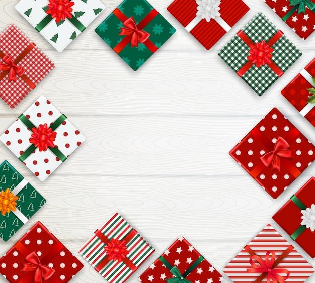 Fondo realista con patrón de cajas de navidad decoradas en mesa de madera blanca