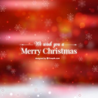 Fondo rojo de navidad desenfocado con copos de nieve