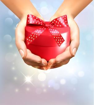Fondo de vacaciones con manos sosteniendo caja de regalo. concepto de dar regalos.