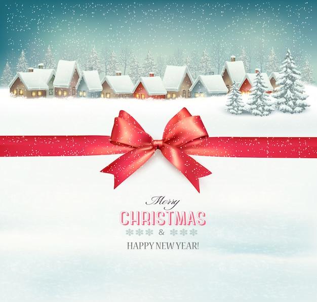 Fondo de vacaciones de navidad con un pueblo y una cinta de regalo roja.