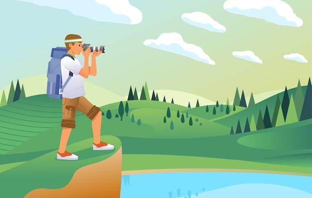 Fotógrafo joven tomando una foto del hermoso paisaje de la colina, el lago y el campo verde