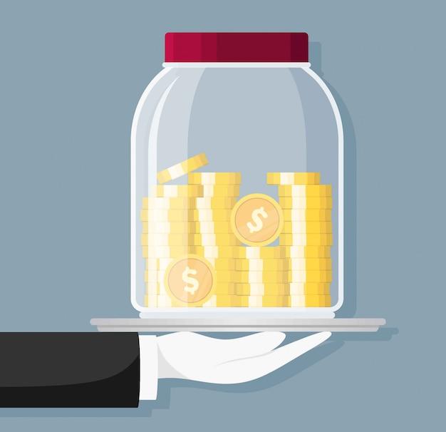 Frasco de dinero de vidrio lleno de monedas de oro y de la mano. ahorro de moneda de un dólar en hucha. crecimiento, ingresos, ahorro, inversión. símbolo de riqueza. éxito en el negocio.