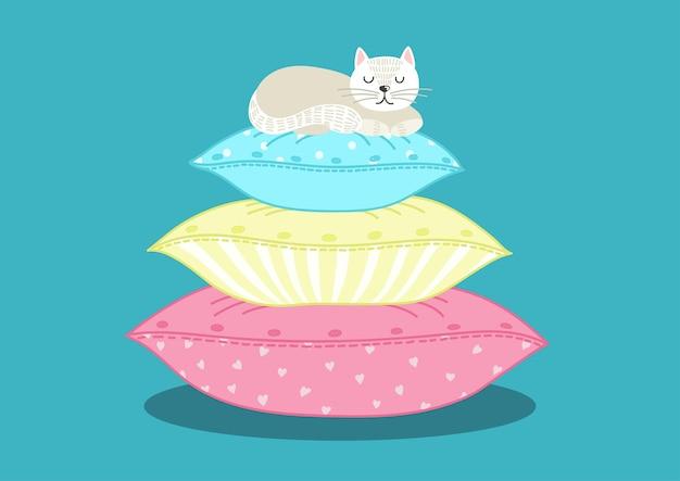 Gato blanco durmiendo sobre una pila de almohadas.