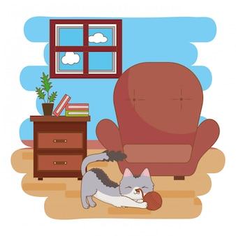 Gato jugando con ovillo de lana en la sala de estar