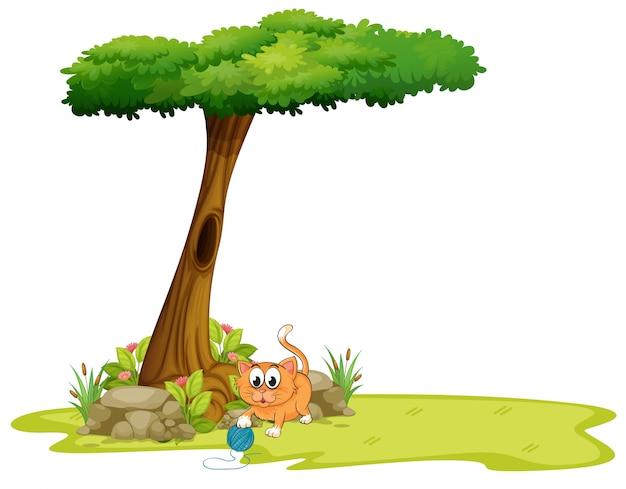 Un gato naranja jugando bajo el árbol