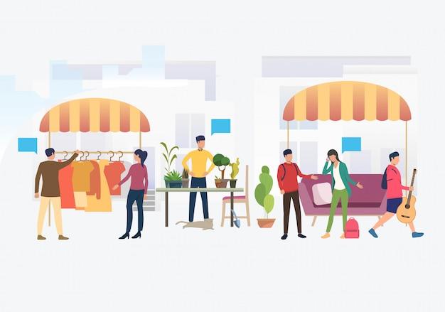 Gente comprando y vendiendo ropa y plantas al aire libre.