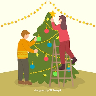Gente decorando el árbol de navidad en interiores