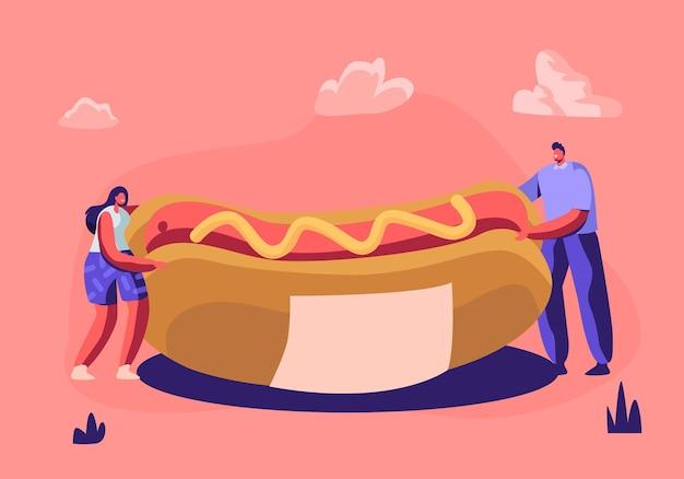 Gente diminuta sosteniendo un enorme perrito caliente con mostaza amarilla. linda escena en miniatura de trabajadores de café o visitantes con comida rápida.