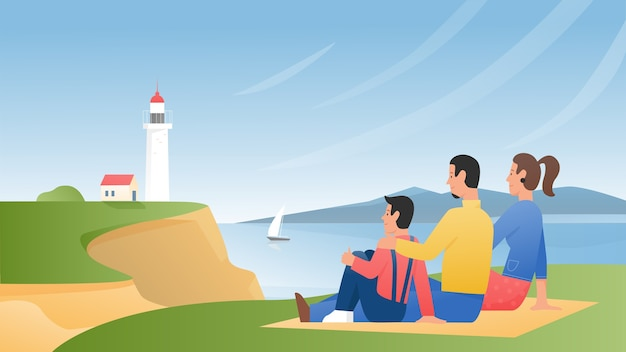 La gente de la familia disfruta de la naturaleza, el paisaje y la vista del faro, sentados sobre la hierba verde en la orilla del mar