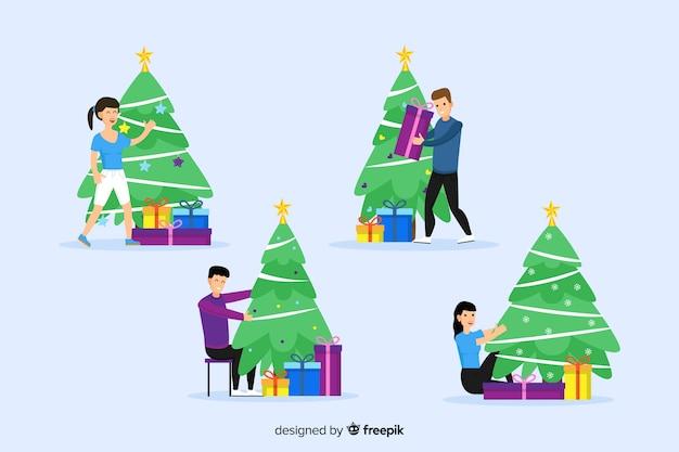 Gente feliz que adorna el árbol de navidad en fondo azul
