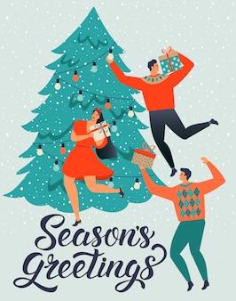 Gente, hombres y mujeres jóvenes decoran una tarjeta de árbol de navidad
