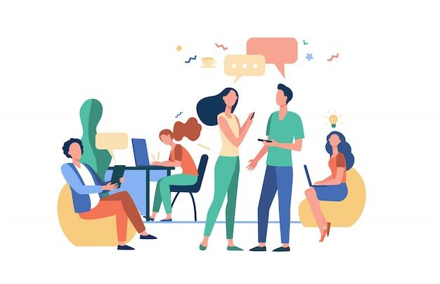 Gente inconformista hablando y usando computadoras en colaboración