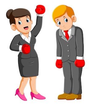 La gente de negocios con guantes de boxeo, la mujer de negocios gana y los hombres de negocios pierden