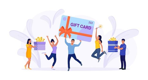 Gente pequeña alegre con tarjeta de regalo grande, caja actual. cliente contento con tarjeta de descuento, cupón, vale, certificado. obtenga puntos del programa de lealtad y obtenga recompensas y obsequios o bonificaciones en línea
