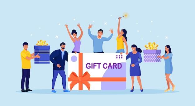 Gente pequeña y alegre con tarjeta de regalo grande. cliente contento con tarjeta de descuento, cupón, vale, certificado. obtenga puntos del programa de lealtad y obtenga recompensas y obsequios o bonificaciones en línea