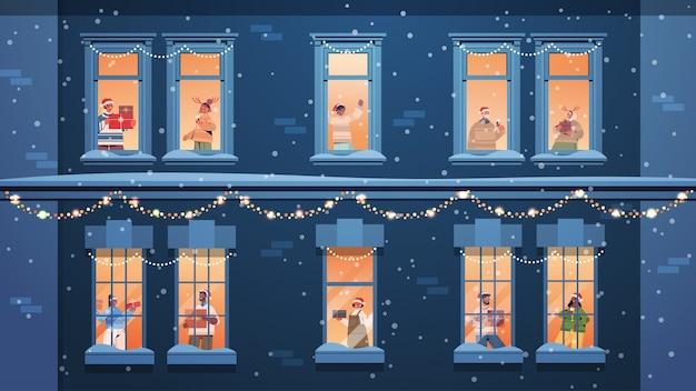 Gente con sombreros de santa sosteniendo regalos mezcla vecinos raza de pie en los marcos de las ventanas año nuevo vacaciones de navidad celebración concepto de autoaislamiento edificio fachada de la casa ilustración vectorial horizontal