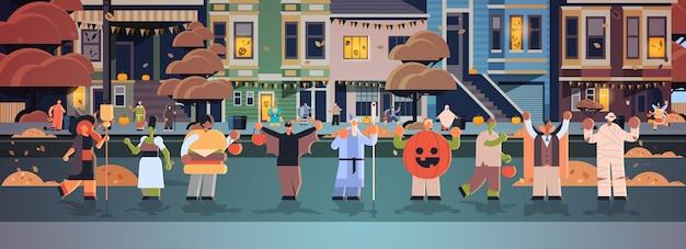 Gente vestida con diferentes disfraces de monstruos caminando en la ciudad trucos y golosinas feliz celebración de la fiesta de halloween concepto ciudad calle edificios paisaje exterior