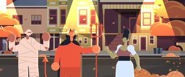 Gente vestida con disfraces de diablo zombie momia caminando en la ciudad trucos y trato feliz celebración de fiesta de halloween concepto noche ciudad calle edificios exterior paisaje urbano