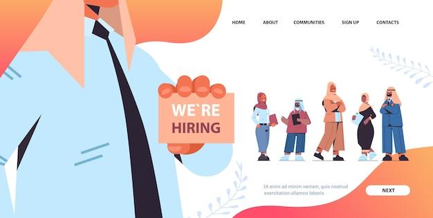 Gerente de recursos humanos árabe sosteniendo estamos contratando cartel eligiendo empresarios árabes solicitantes vacante concepto de contratación abierta espacio de copia horizontal ilustración vectorial