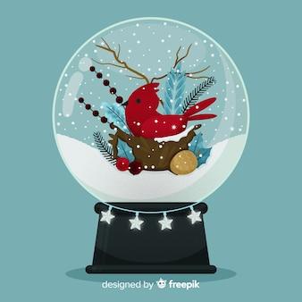 Globo de bola de nieve de navidad de diseño plano con pájaro